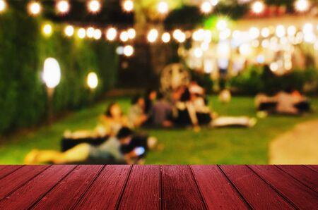 lege houten vloer of terras met wazig beeld van stedelijke nachtlicht bokeh van nacht muziekfestival met mensen in de tuin, kopie ruimte voor weergave van productpresentatie, vintage kleurtoon