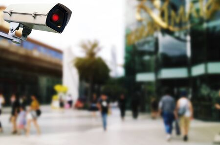 private security: CCTV, security outdoor camera system operating with blurred image of people walking at department store shopping mall, surveillance security and safety technology concept