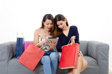 two young friends asian woman watching special offer in her tablet with shopping bags on sofa at home white background, lifestyle smart internet technology, online shopping and payment online concept