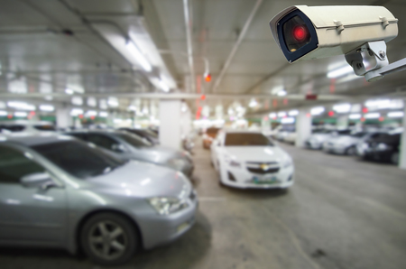 CCTV security indoor camera system operating with blurred image of under ground indoor car parking garage area, RFID solution management system, surveillance security and safety technology concept