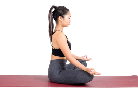 side view of young asian woman doing yoga in Padmasana or Lotus yoga pose on the mat isolated on white background, exercise fitness, sport training, healthy lifestyle concept Stock Photo