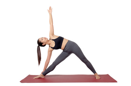 young asian woman doing yoga in Trikonasana or Triangle pose on mat isolated on white background, exercise fitness, sport training, healthy lifestyle concept Stock Photo
