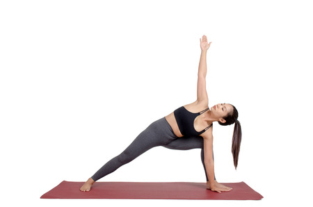 young asian woman doing yoga in Utthita Parsvakonasana or Extended Side Angle pose on mat isolated on white background, exercise fitness, sport training, healthy lifestyle concept Stock Photo
