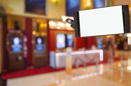 CCTV and LCD TV with white blank screen or billboard for your text message or media content with blurred image of ticket sales counter at movie theater, advertising, commercial and marketing concept Stock Photo