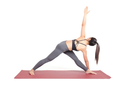 young asian woman doing yoga in Parivrtta Trikonasana or Revolved Triangle yoga pose on the mat isolated on white background, exercise fitness, sport training and healthy lifestyle concept