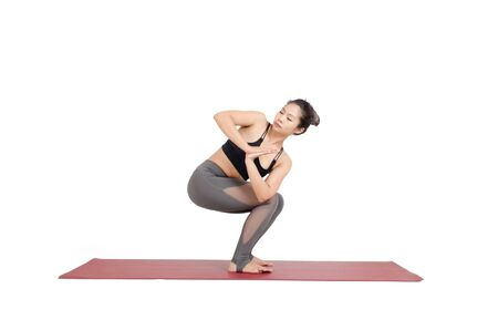 young asian woman doing yoga in Revolved Chair asana yoga pose, Parivrtta Utkatasana pose on the mat isolated on white background, exercise fitness, sport training, healthy lifestyle, people concept