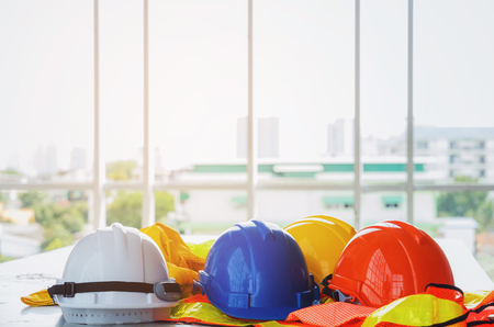 white, orange, yellow and blue safety helmet with reflective clothing on desk at construction site and scaffold background, engineer, safety, industry and construction building concept