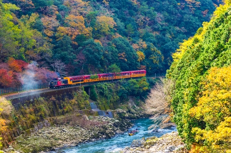 beautiful mountain view in colorful autumn season with sagano scenic railway or romantic train on bridge and boat in the river in Arashiyama, Kyoyo, Japan Stockfoto