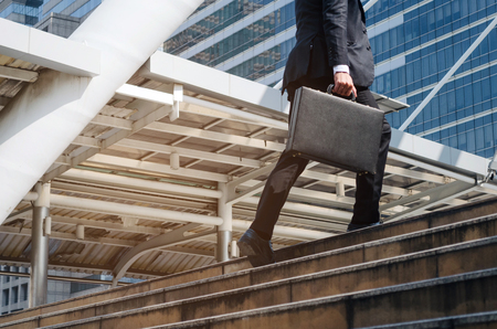 young handsome business man holding briefcase and walking up the stairs going to work time at morning in the city, determination, confidence, lifestyle, rush hour, grow up and successful concept Stock Photo