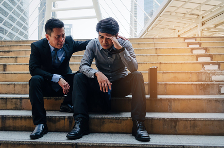 medium aged asian business man upset about life problems with support from his best friend and sitting on walkway in modern city, fired from job, unemployment, financial and investment concept