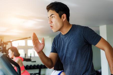 hombre asiático joven muscular ejercitando sus piernas cardio corriendo en cinta y potente gritos gritando en gimnasio, culturista, estilo de vida, ejercicio fitness, entrenamiento y deporte concepto de entrenamiento