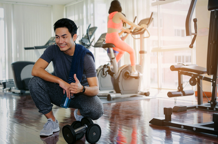 muscular asian young handsome man with dumbbell and towel showing thumbs up while resting after workout for good healthy in fitness gym, bodybuilder, lifestyle, exercise and sport training concept 스톡 콘텐츠