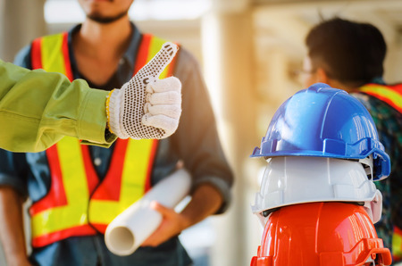 hand with glove of engineer or technician showing thumbs with white, orange and blue safety helmet stacked with in construction site building, industry, teamwork, successful and construction concept