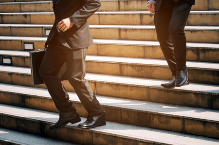 midsection young handsome business man holding briefcase and walking fast down stair going to work time at morning in city, determination, confidence, lifestyle, rush hour, grow up, successful concept