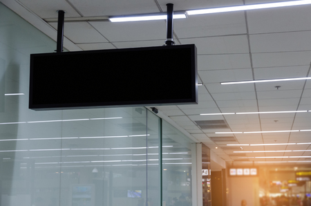 hanging black advertising billboard or light box showcase on wall at airport or subway train station, copy space for your text message or media content, advertisement, commercial and marketing concept Banque d'images