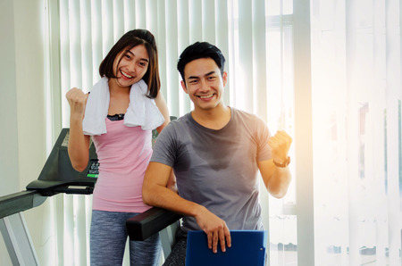 young happy smile asian woman slim body with towel and muscular personal trainer man with clipboard showing cheer up hand while resting after workout in fitness gym, healthy, exercise, sport concept