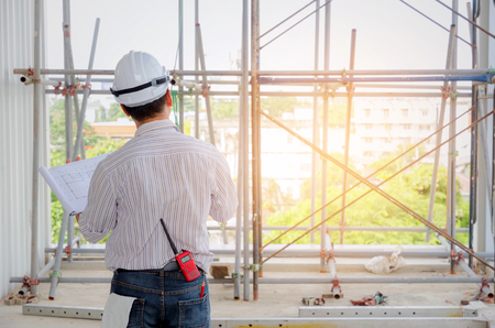 back view of smart engineer, architect or technician with white safety helmet holding blueprint in construction site building to greeting start up project, successful, business, industry concept