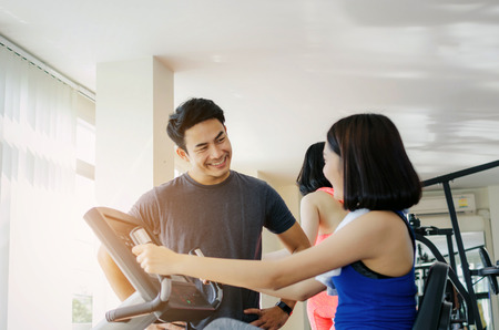 muscular handsome personal trainer man talking with young asian woman slim body with towel and exercising his legs cardio training on bicycle in fitness gym for good healthy, lifestyle, sport concept