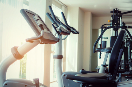 bicycle machine or treadmill machine, exercise machine and gym equipment in empty fitness gym center, bodybuilder, lifestyle, exercise fitness, workout and sport concept, sunlight effect at morning