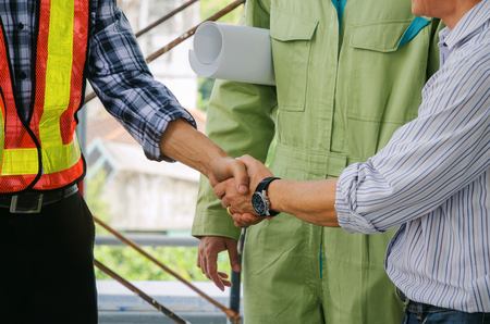 engineer and technician contractor shaking hands after finishing up a business meeting to greeting start up project contract in construction site building, successful, partnership, teamwork concept Stock Photo