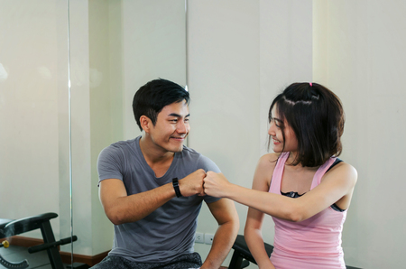 muscular young handsome man joining hands together with asian woman slim body while resting after workout in fitness gym, love couple, personal trainer, bodybuilder, lifestyle, sport exercise concept Stock Photo