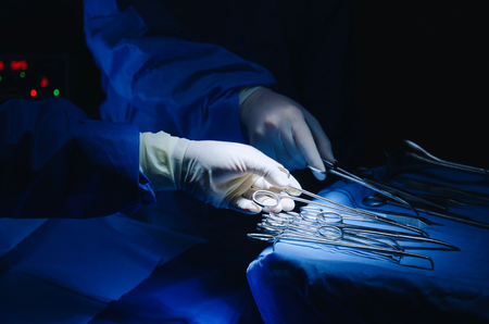 close up surgeons hand taking scissors, forceps and surgical instruments on table for operation with colleagues performing work in operation room at hospital, emergency case, surgery, medical concept