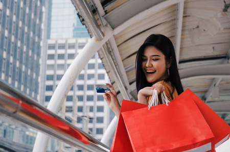 young beautiful woman holding many colorful red shopping bags and credit card walking in modern big city, fashion, promotion, special offer, summer sale, people, payment and shopping online concept