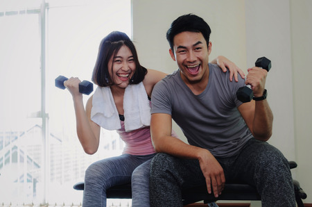 young asian sporty man and woman love couple doing exercises with dumbbell, cheer up and smiling after good workout in fitness gym, slim bodybuilder, healthy lifestyle and sport training concept Stockfoto