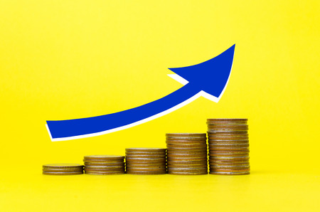 blue arrow up with money coin stack growing graph on yellow background, investment, financial, stock market, marketing, business plan and saving money concept