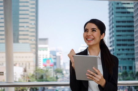 beautiful happy young asian business woman smiling wearing modern black suit cheer up hand with mobile tablet in building city background, network technology, internet, financial, investment concept