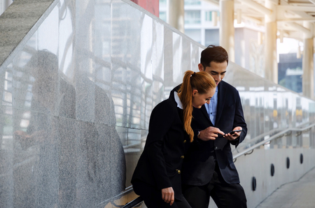 business man and woman holding mobile phone and talking standing in modern city, social network, internet, successful, financial, investment, support, partner, teamwork, community, connection concept