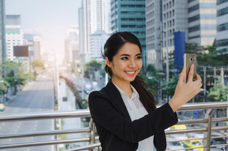 young asian business woman smiling wearing modern black suit video conference with mobile phone in building city background, network technology, internet, digital financial and investment concept Stock Photo