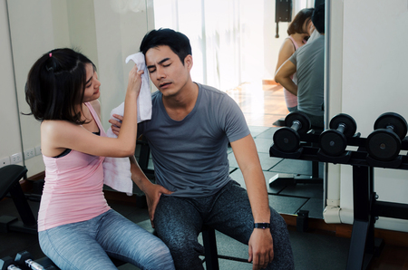 young asian woman helping wipes sweat off muscular young handsome man face while resting after workout in fitness gym, love couple, personal trainer, bodybuilder, lifestyle and sport exercise concept