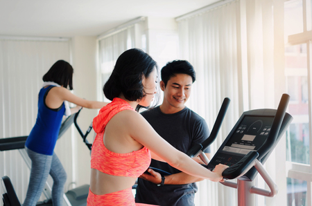asian young woman slim body exercising on bicycle machine with young man personal trainer in fitness gym, bodybuilder, healthy lifestyle, fitness, workout and sport training concept Stock Photo