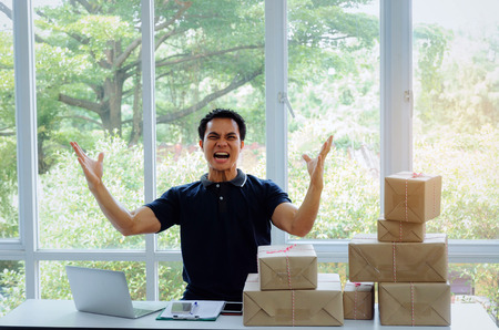 Start up. young man happy after new order from customer with laptop computer, mobile phone, delivery packaging box on table, small business owner working at home office, SME, shopping online concept