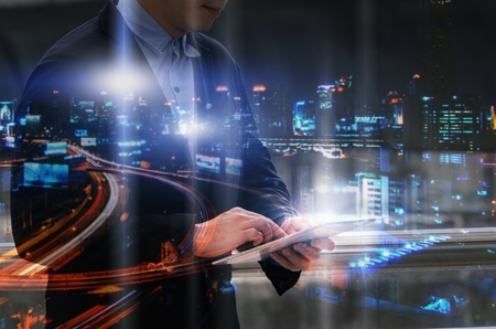 double exposure of handsome business man using mobile tablet with modern night city background, financial, investment, cyber, security system, network technology, internet and digital concept