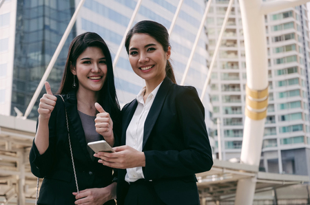 smiling business woman holding mobile phone and giving thumbs up as like sign standing together in modern city, professional employees, successful, support, partner, teamwork and community concept Stock Photo