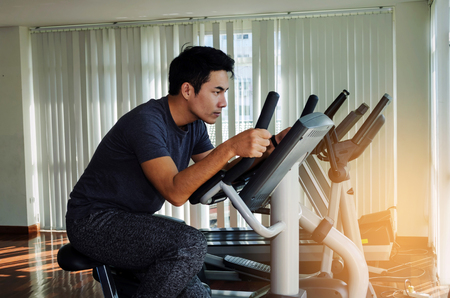 muscular young asian man exercising his legs cardio training on bicycle in fitness gym for good healthy at the morning, bodybuilder, lifestyle, exercise fitness, workout and sport training concept Stock Photo