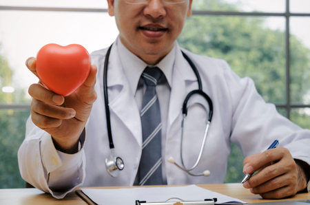 doctor or pharmacist with stethoscope on neck sitting at worktable with clipboard and holding red heart in hospital or clinic, heart attack, medical technology, disease treatment, health care concept