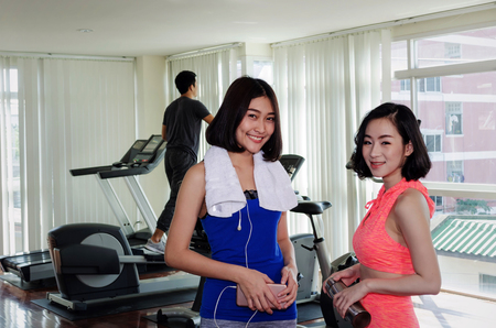 two happy smiling asian young woman slim body with towel in fitness gym at morning with people on machine bicycle background, bodybuilder, healthy lifestyle, exercise, workout, sport training concept Stock Photo