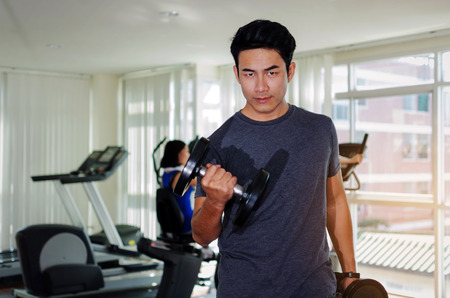 muscular asian young handsome man doing exercises with dumbbell for good healthy in fitness gym at morning with people background, bodybuilder, lifestyle, exercise workout and sport training concept