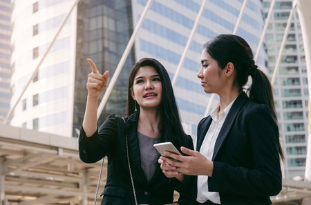 business woman holding mobile phone and talking with partner while standing in modern city, professional employees, successful, support, partner, teamwork, community and connection concept