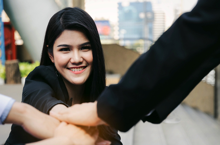beautiful young business woman joining hands with group of business people team together in the modern city, team leader, successful, support, meeting, partner, teamwork and connection concept Stock Photo