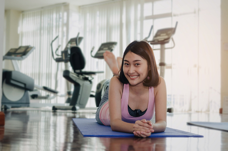 young pretty asian woman slim body smiling relaxing and lying on floor with yoga mat after workout in fitness gym at morning, motivation, good health, healthy lifestyle, exercise and workout concept