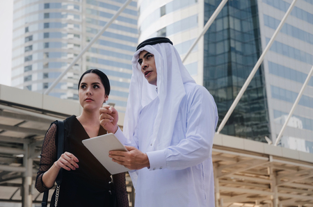 young handsome Arabian business man in white suit holding mobile tablet with secretary asian woman in modern city, financial, investment, teamwork, company success and business growth concept