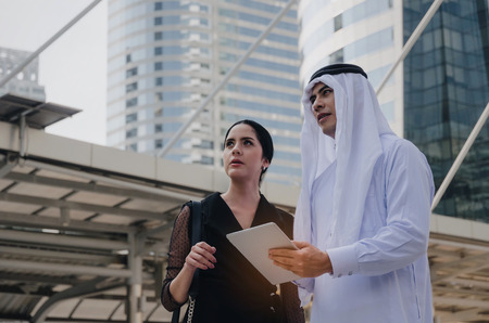 young handsome Arabian business man in white suit holding mobile tablet with secretary asian woman in modern city, financial, investment, teamwork, company success and business growth concept Stock Photo - 106624189