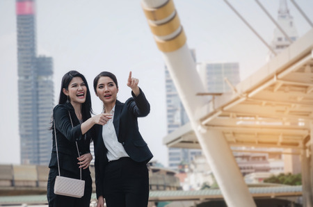 smiling business woman holding mobile phone and talking with partner while standing in modern city, professional employees, successful, support, partner, teamwork, community and connection concept Stock Photo