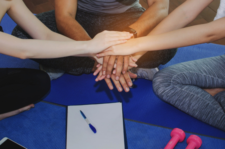 close up of sport people team planning to reach their goal and doing high five together sitting on yoga mat in fitness gym, exercise, training, workout, partnership, success and teamwork concept