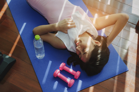 asian young pretty woman slim body with white towel relaxing and lying on floor with yoga mat, dumbbell and water bottle in fitness gym at morning, healthy lifestyle, exercise and workout concept Stock Photo