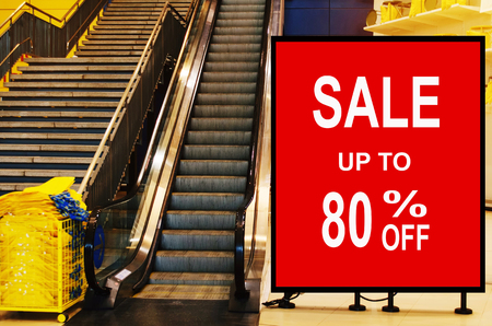 big sale 80% mock up advertise billboard or advertising light box in front of escalator in modern department store shopping mall, special offer, commercial, marketing and advertisement concept